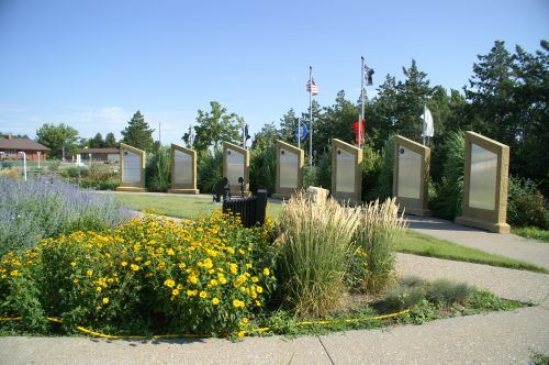 Memorial Garden with flowers in front and flags in the background